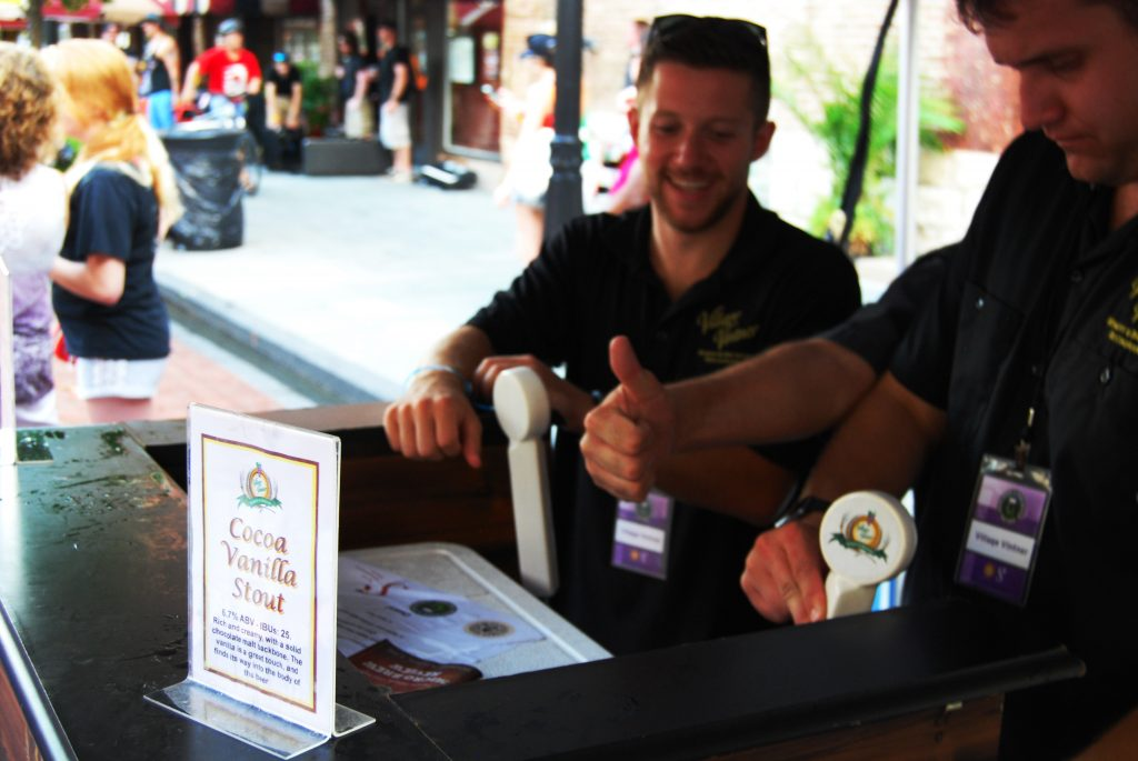 Village Vintner pouring the Cocoa Vanilla Stout, with an enthused worker's hand.